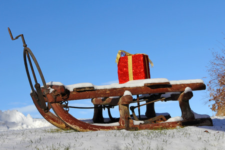 A Christmas sleigh in the snow. A Santa Claus sled with a red gift