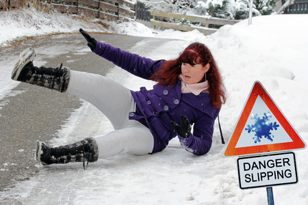 Accident danger in winter. A woman has slipped and has fallen down