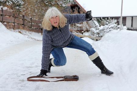 Ongeval gevaar in de winter. Een vrouw glipt uit op de gladde straat Stockfoto