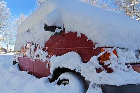 A snowed red car. Winter in the road