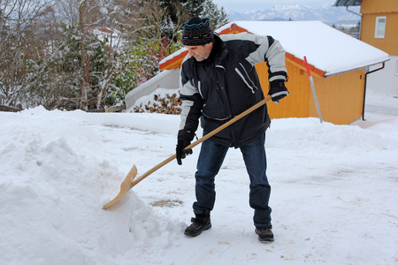 A man shovels snow of the street in winter. A man shovels snow