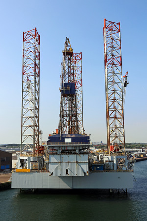 An oil rig in a harbor by the sea. A drilling rig in the sea