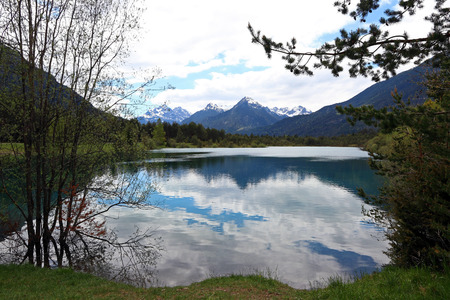 Clouds are reflected in a blue-turquoise lake at Weissenbach am Lech in Austria