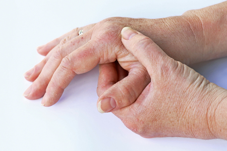 An elderly woman has pain in her hands
