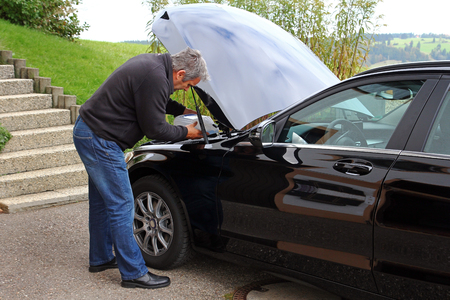 A man refills windscreen wiping water on a car