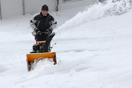 A man clears snow in winter. Snow clearing with the snow mill Stock Photo