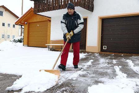 Een man schept sneeuw voor de garages