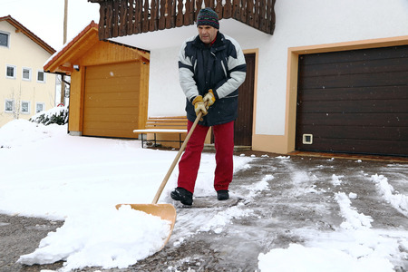 A man shovels snow in the front of the garages