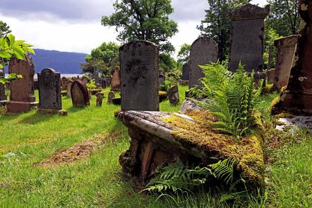Oude graven en grafstenen op een begraafplaats in Schotland