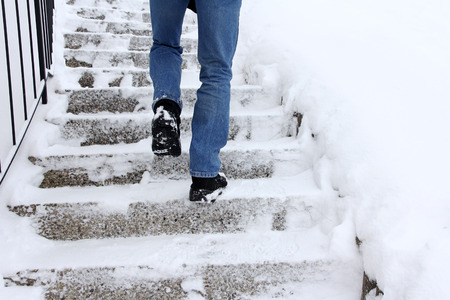 Risk of slipping when climbing stairs in winter. A man goes up a snow-covered staircase Foto de archivo