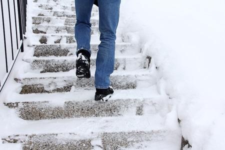 Risco de escorregar ao subir escadas no inverno. Um homem sobe uma escadaria coberta de neve Foto de archivo - 92165269
