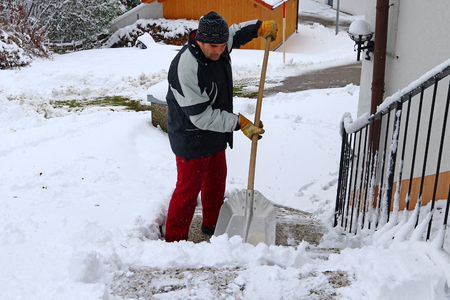 A man shovels snow in a staircase in front of a house in winter time