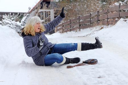 Eine Frau rutscht auf der Winterstraße . Fallen auf rutschigen Straßen Standard-Bild - 92766667