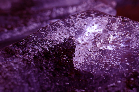 A piece of ice with frozen bubbles in the water in ultra violet.