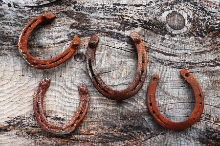 Four old rusty horseshoes on wooden ground. Horseshoe as lucky charm
