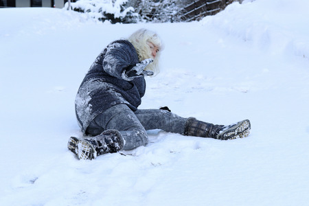 A woman slips on the winter road. Fall on slippery roads Banque d'images - 95580869