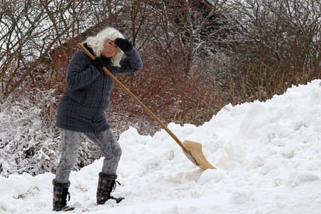 Clearing snow is very stressful for a woman. A woman is strained by the snow shoveling