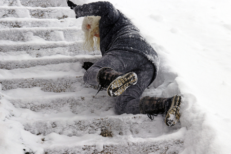 A woman slips and fell on a wintry staircase. Fall on smooth steps 스톡 콘텐츠