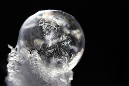 A frozen soap bubble on snow is a beautiful natural work of art Stock Photo
