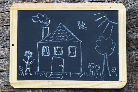 A house with a garden - drawn on a board. Single family house with garden on a chalkboard Stock Photo