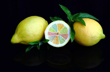 Fresh lemons with colorful pieces of fruit and peppermint. Sour is tasty, healthy and colorful