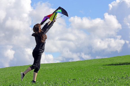 A woman wants to fly a kitten in autumn. Leisure sport with kites on a windy autumn day