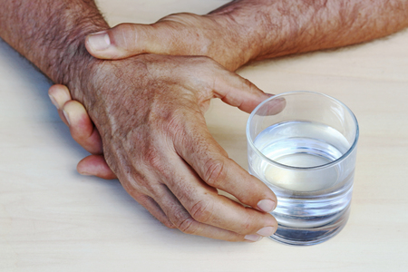The hands of a man with Parkinson's disease tremble. Strongly trembling hands of an older man Stock Photo