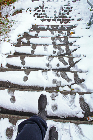 In winter there is a danger of slipping on a snow-covered staircase. A woman wants to go down a slippery staircase Stock fotó