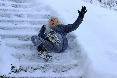 A woman slips and fell on a wintry staircase. Fall on smooth steps Stock fotó