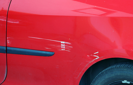 Paint scratches on a red car. Accidental damage to a red car