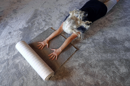 A woman is happy about her new soft carpet. A woman happily reads on her new carpet. Reklamní fotografie - 112026802