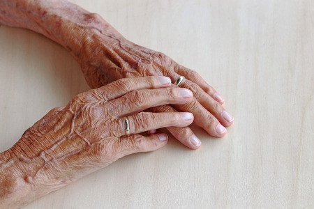 The hands of a very old woman. Old woman's hands on a table. Old woman's hands with veins