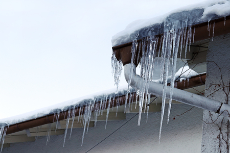 Large icicles hanging from a house roof. Dangerous large icicles on a house