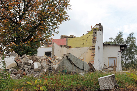An old damaged house is torn down. Demolition of a broken house