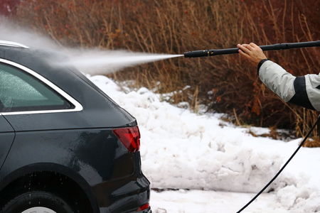 A man washes the dirt and salt off his car in winter. 版權商用圖片