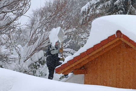 A man removes heavy snow from the roof of a house. Dangerous weight on a roof Stock Photo