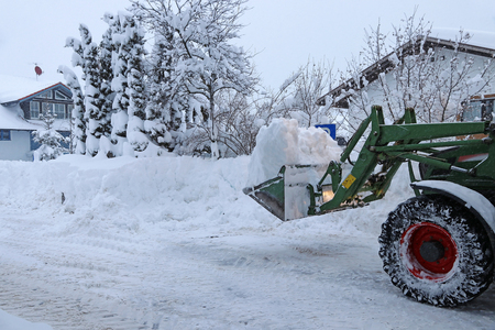 Snow clearing a road with a tractor. In winter the road is cleared with a tractor.