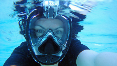 A young woman with a diving mask snorkeling in the sea