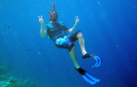 A man with diving goggle and fins snorkeling underwater