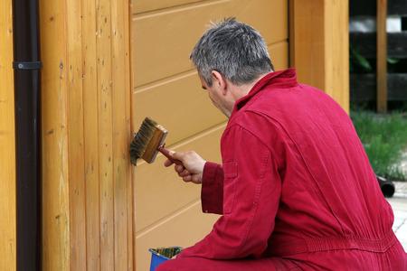 A man paints a garage with a wood preservative paint.