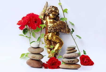 A golden angel with red roses, ivy and stone towers