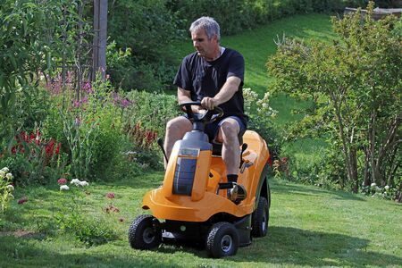 A man mows the lawn with a ride-on lawnmower. Mowing the lawn in summer