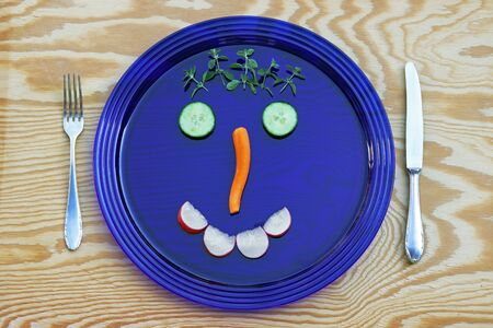 A blue glass plate with a vegetable face.