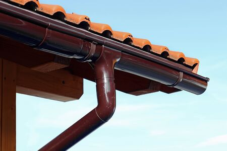 Gutter on a wooden garage. A wooden house with roof tiles and rain gutter.