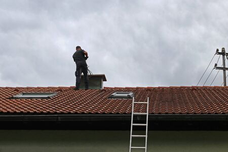 A chimney sweeper on the roof cleans a chimney with a brush. 版權商用圖片 - 128849873