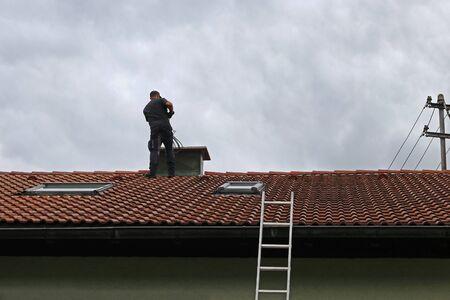 Een schoorsteenveger op het dak reinigt een schoorsteen met een borstel.