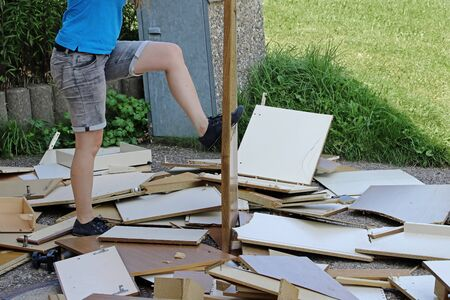 A woman smashes furniture on the floor. Angry woman smashes furniture