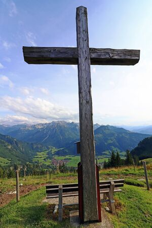 A summit cross in the Alps. A summit cross in the Allgaeu Alps. A summit cross in the evening light against the sky. Фото со стока