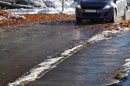 Accident hazard for cars by wet leaves and snow on the road