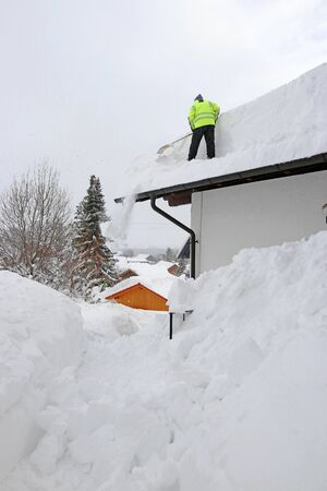 A man shovels dangerously heavy snow from a house roof Фото со стока - 133001865